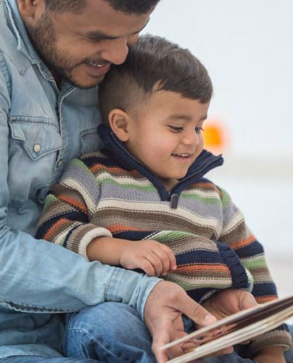 Photo of a father reading a book for his son