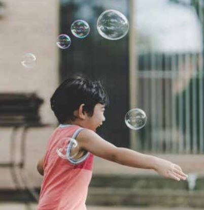 Photo of a child playing with bubbles
