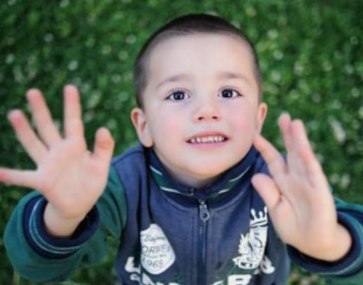 Photo of a boy showing his hands